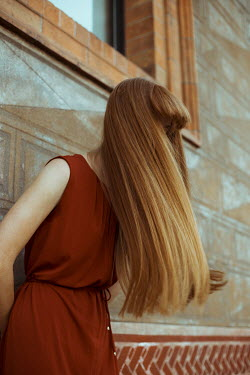Greta Larosa Young woman with long hair leaning on wall