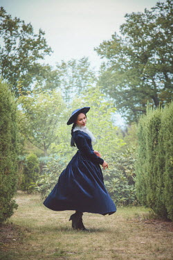 Joanna Czogala Young woman with Victorian dress and hat in garden