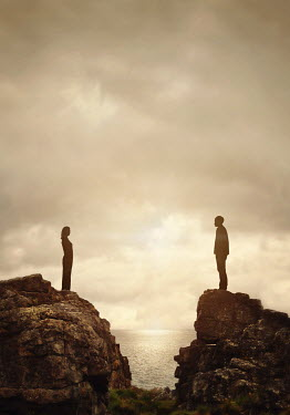 Lyn Randle Silhouette of separated man and woman standing on rocks Couples