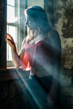 Stephen Carroll Young woman in red crop top looking out window