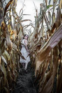Stephen Carroll Young woman walking in corn field Women