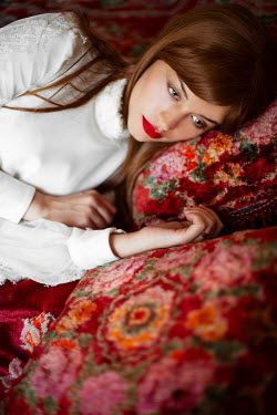 Ebru Sidar Young woman lying on floral pattern cushion