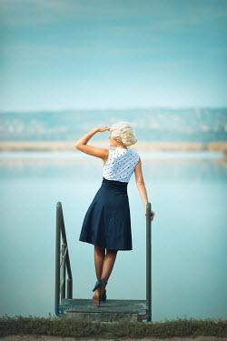 Ildiko Neer Vintage woman standing by lake Women