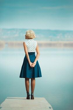 Ildiko Neer Vintage woman standing on jetty by water