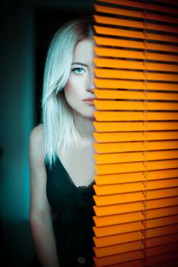 Nilufer Barin Young woman behind orange blinds Women
