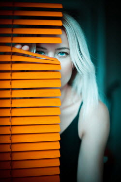 Nilufer Barin Young woman behind orange blinds