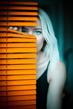 Nilufer Barin Young woman behind orange blinds
