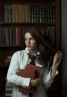 Robin Macmillan Teenage girl holding books in library
