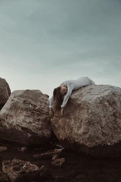 Greta Larosa DEAD WOMAN LYING ON LARGE ROCKS Women