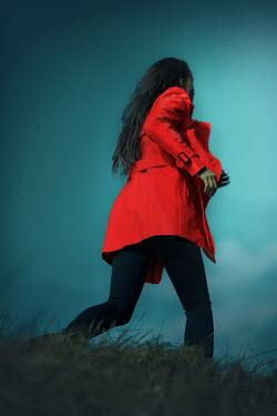 Ildiko Neer Woman in red coat running in grass