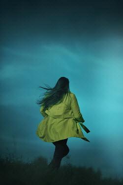 Ildiko Neer Woman in yellow coat running in grass