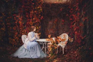 Beata Banach DAYDREAMING WOMAN SITTING IN GARDEN IN AUTUMN Women