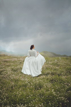 Joanna Czogala HISTORICAL WOMAN STANDING IN STORMY COUNTRYSIDE Women