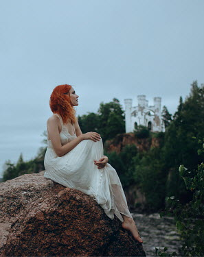 Irina Orwald WOMAN WITH RED HAIR ON ROCK BY CASTLE Women