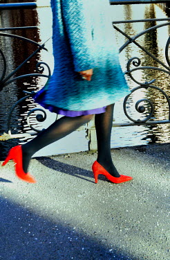 Ute Klaphake WOMAN IN RED SHOES WALKING BY RIVER Women