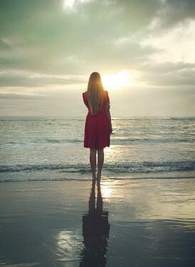 Mark Owen BLONDE GIRL STANDING ON BEACH AT DUSK Women