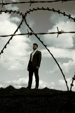 Miguel Sobreira MAN IN SUIT OUTDOORS WITH BARBED WIRE Men