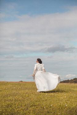 Joanna Czogala HISTORICAL WOMAN STANDING IN WINDY FIELD Women