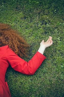 Joanna Czogala WOMAN WITH RED HAIR LYING ON GRASS Women
