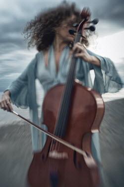 Alex Maxim WOMAN PLAYING CELLO ON BEACH AT DUSK Women