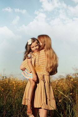 Buffy Cooper WOMAN CUDDLING DAUGHTER IN SUMMERY FIELD Children