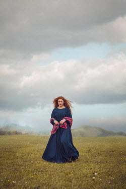 Joanna Czogala Woman with blue dress and scarf in field