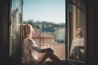 Evelina Kremsdorf Young woman sunbathing in open window Women
