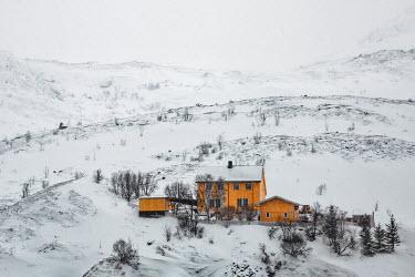 Evelina Kremsdorf Orange house on snowy hill in Lofoten, Norway Houses