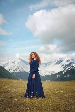 Joanna Czogala Woman in blue dress by snowy mountains