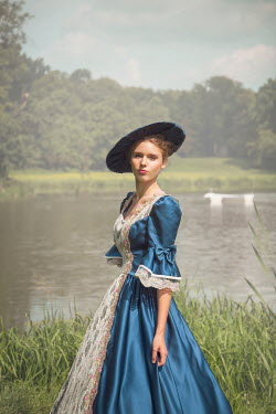 Joanna Czogala Young woman in Victorian dress and hat by pond