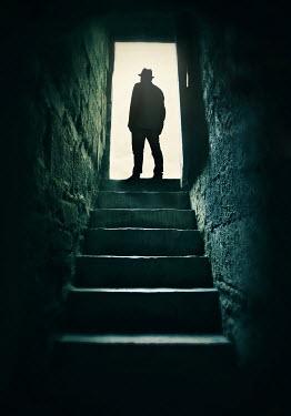 Lyn Randle Silhouette of man in hat and coat standing in doorway