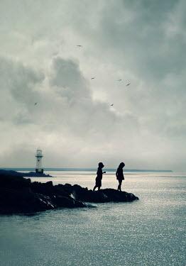 Lyn Randle Silhouette of girls on rocks by sea