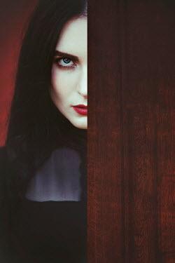Joanna Czogala Young woman with black hair behind wooden door