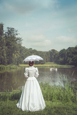 Joanna Czogala Young woman in white dress with parasol by pond