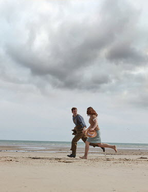 CollaborationJS A ww2 couple running along a sandy beach