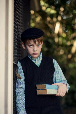 Kelly Sillaste Boy with beret and vest holding books while leaning on fence