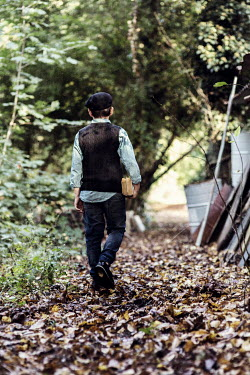 Kelly Sillaste Boy with books walking in forest