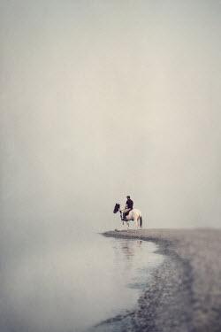 Jaime Brandel Man riding horse on foggy beach Men