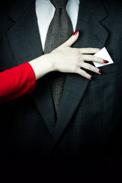 Magdalena Russocka hand of a woman slipping business card into pocket in man's suit
