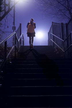 Lee Avison school girl walking alone up steps outdoors at night