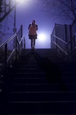 Lee Avison school girl walking alone up steps outdoors at night