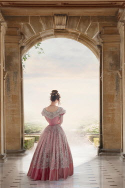 Lee Avison victorian woman in a ball gown walking towards a stone archway