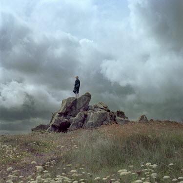Dmytro Baidachnyi Woman standing on rocks under cloudy sky Women