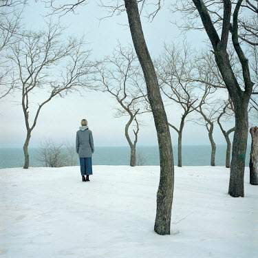 Dmytro Baidachnyi Woman standing on snow watching sea Women