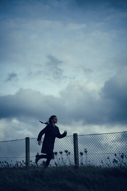Magdalena Russocka modern woman running by wire fence