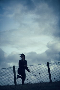 Magdalena Russocka scared modern woman running by wire fence