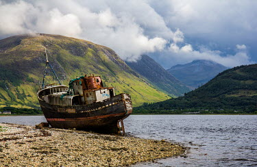 Rodney Harvey Rusted boat on river by mountains