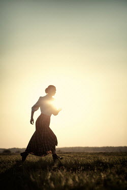 Magdalena Russocka vintage woman running in field at sunset