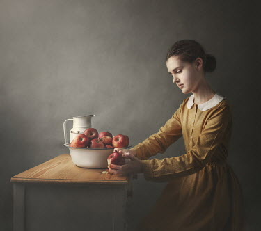 Anna Buczek Young woman sitting at table and peeling apple Women