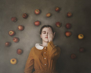 Anna Buczek Young woman lying down amongst apples while covering eye
